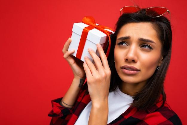 赤に分離されたクローズ アップ美しい感情的な若い黒髪の女性