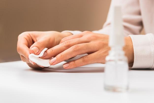 근접 촬영 아름다운 여성 손 목화 패드로 손톱을 청소