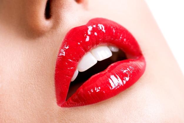 Primo piano belle labbra femminili con rossetto rosso. trucco brillante lucentezza moda glamour.