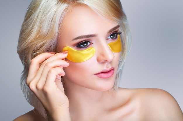 Closeup of beautiful happy smiling woman with moisturizing under eye mask