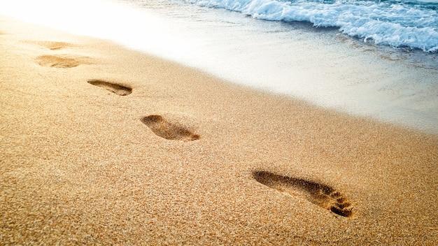 Крупным планом красивое изображение человеческих следов на мокром песке на морском пляже на фоне красивого заката над поверхностью воды