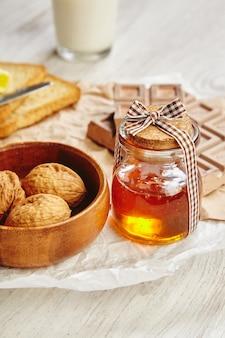 朝食の朝の光の中で白いクラフト紙に贈り物としてひもで締められた木製の帽子と蜂蜜とクローズアップの美しい瓶。