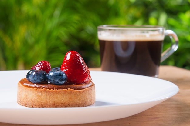 Closeup of beautiful mini tart with berries and cup of coffee