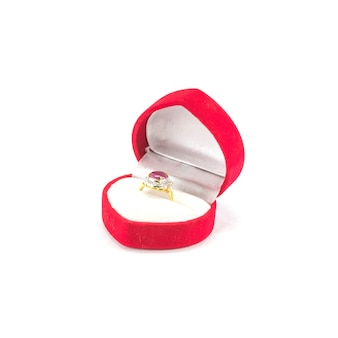 Closeup beautiful pink pebble ring in red heart shape box isolated on white