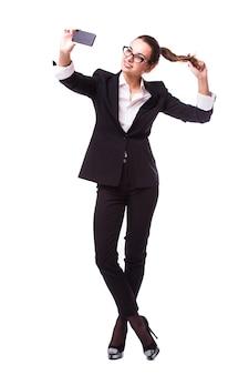 Closeup of beautiful playful business woman making selfie photo on isolated white wall