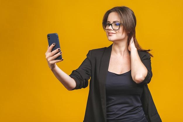 Closeup of beautiful playful business woman making selfie photo