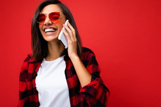 クローズアップスタイリッシュな赤いシャツ白いtシャツと分離された赤いサングラスを身に着けている美しいポジティブな若いブルネットの女性