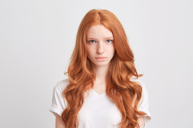 Closeup of beautiful redhead young woman with wavy long hair and freckles wears t shirt feels sad and looks to the front isolated over white wall