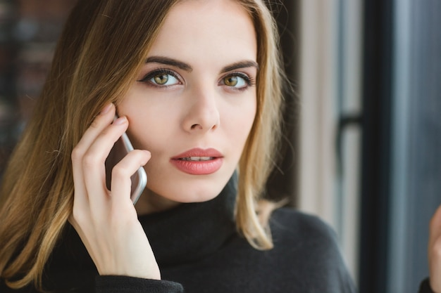 Closeup of beautiful serious young woman talking on cell phone