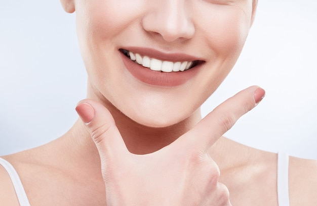 Closeup of beautiful snow-white smile. ideal strong white teeth, teethcare. healthcare, stomatological concept for dentists. only smile on face, fingers near face