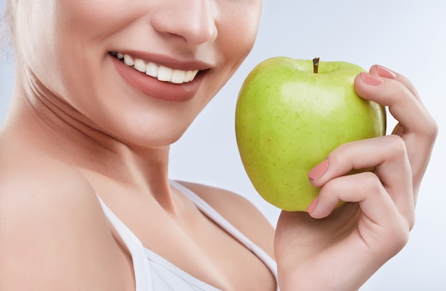 Closeup of beautiful snow-white smile. ideal strong white teeth, teethcare. healthcare, stomatological concept for dentists. only smile, holding green apple near mouth