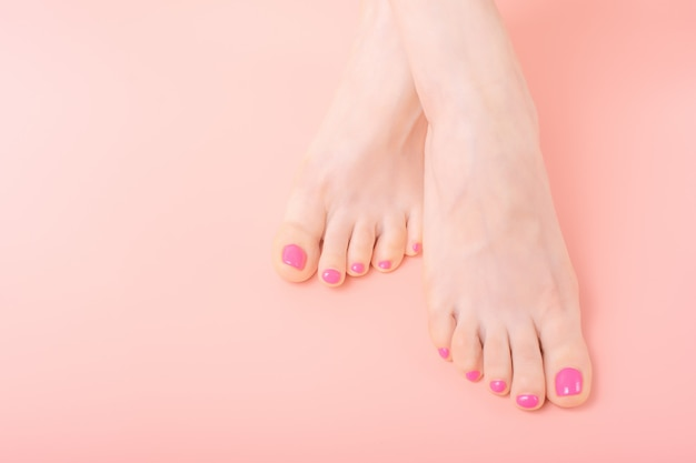 Closeup beautiful well groomed female legs with bright pedicure on a pink background, copy space, skincare concept