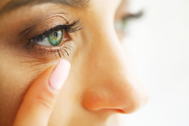 Closeup of beautiful woman applying eye lens in eye