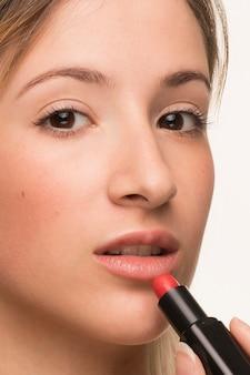 Женщина крупного плана кладя на губную помаду