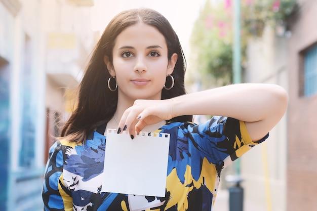 Closeup of a beautiful woman showing a blank notepad.
