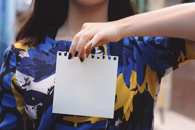 Closeup of a beautiful woman showing a blank notepad.