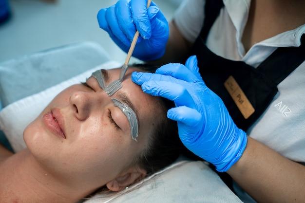 Closeup beautiful woman in spa salon receiving epilation or correction eyebrow using sugar - sugaring