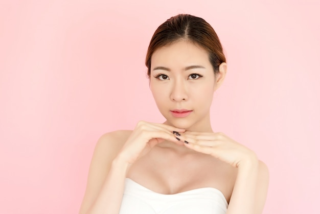 Closeup beautiful young asian woman face isolated on pink