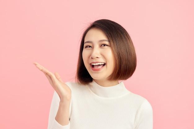 ピンクの背景の上のジェスチャーを示すとクローズアップ美しい若いアジアの女性