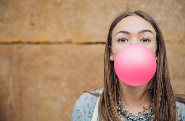 Closeup of beautiful young brunette teenage girl blowing pink bubble gum over a stone wall