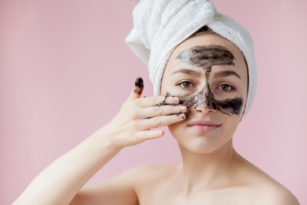 Closeup beautiful young female with black peel off mask on skin