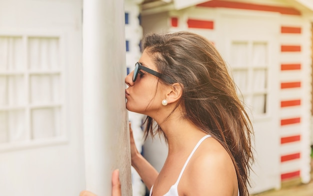 Closeup of beautiful young surfer woman with white top and sunglasses kissing her lovely surfboard