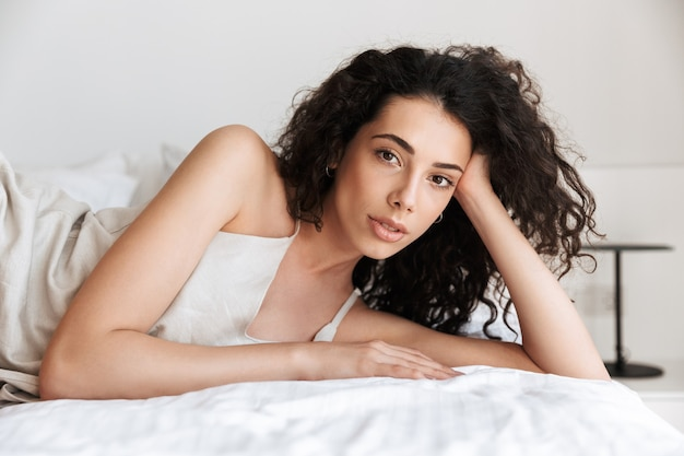 Closeup beautiful young woman 20s with long curly hair wearing silk leisure clothing lying in bed at home, and looking at you while propping up her head with hand