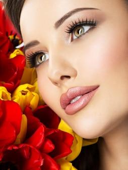 꽃을 가진 젊은 여자의 근접 촬영 아름다움 얼굴. 빨간색과 노란색 튤립과 매력적인 모델