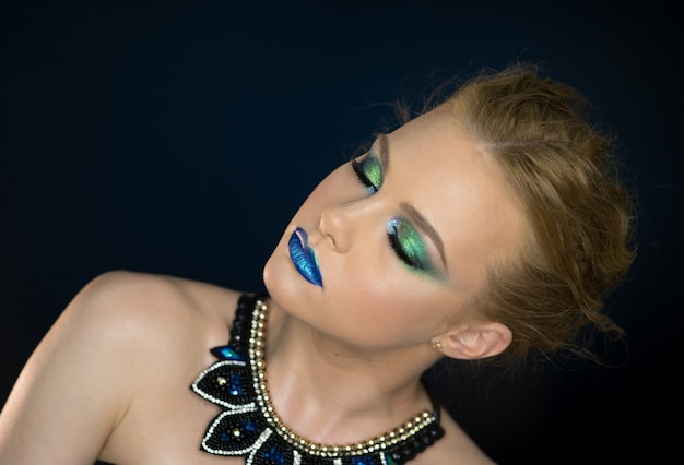 Closeup beauty portrait of attractive model face with bright visage. multicolored eye makeup and pink lips make-up