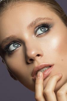 青い目と暗い夜のメイクの女の子のクローズアップの美しさの肖像画。高品質の写真