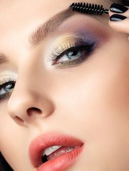 彼女の眉毛をとかす女性のクローズアップの美しさの肖像画