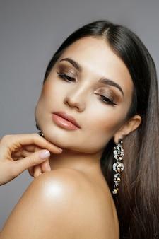 光沢のある髪と裸の肩でポーズをとる完璧な肌を持つ素晴らしい女性のクローズアップの美しさの肖像画