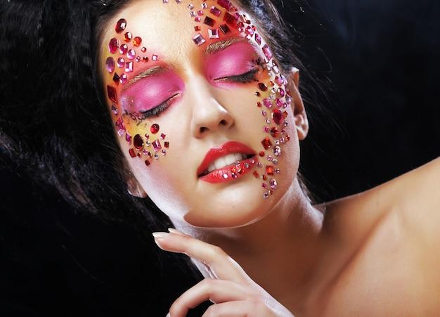明るいラインストーンの顔を持つ魅力的なモデルの顔のクローズアップの美しさの肖像画。目を閉じた女性。