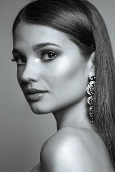 光沢のある髪と裸の肩でポーズをとる完璧な肌を持つ素晴らしい女性のクローズアップの美しさの肖像画。黒と白の調子を整える