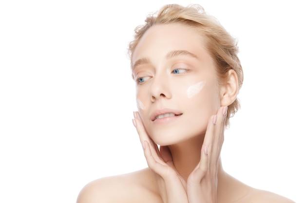 Портрет красоты крупным планом красивой молодой женщины, применяя крем для лица
