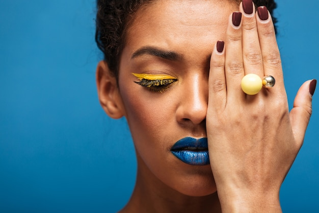 Closeup beauty relaxed mixed-race woman with fancy makeup posing on camera covering one eye with hand, isolated over blue wall