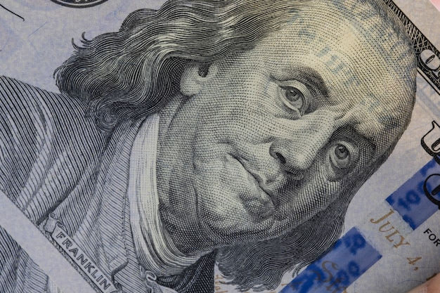 Closeup benjamin franklin face on one hundred us dollar banknote.