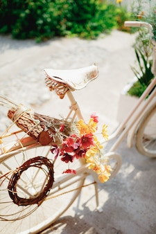 Closeup of bicycle saddle with colorful flowers and log on trunk