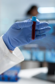 Closeup of biologist researcher man holding medical vacutainer with blood sample