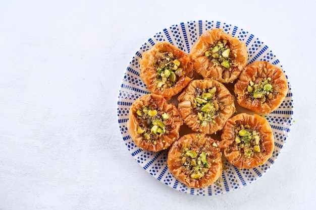 Closeup of birds nest baklava with pistachios on a lightt table with space for text. top view.