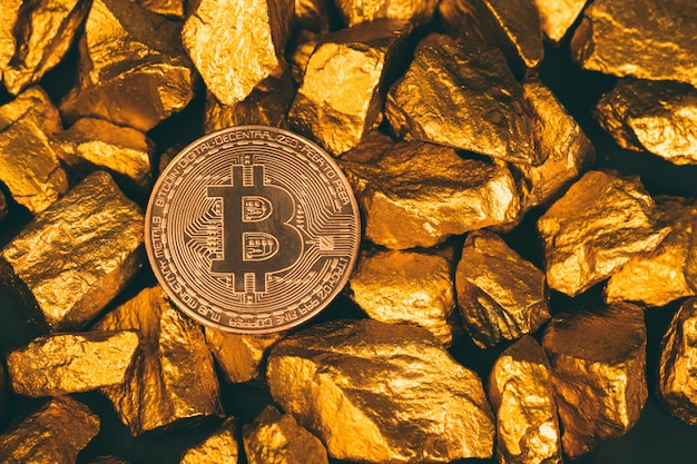 Closeup of bitcoin digital currency and gold nugget or gold ore on black background, precious stone or lump of golden stone