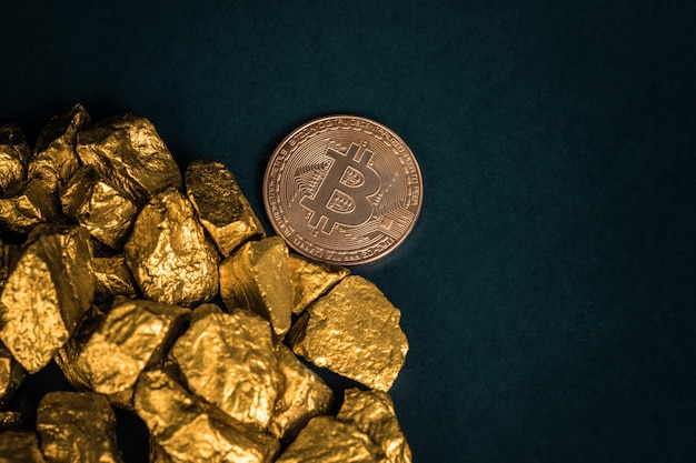 Closeup of bitcoin digital currency and gold nugget or gold ore on black background
