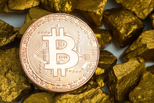 Closeup of bitcoin digital currency and gold nugget or gold ore on white background, precious stone or lump of golden stone