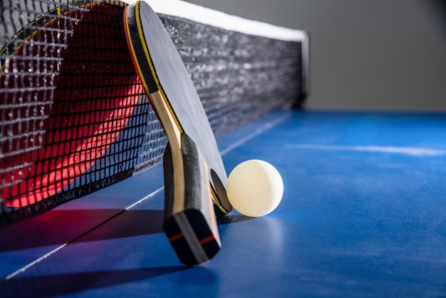 검은색과 빨간색 탁구 라켓이 파란색 탁구대에 있는 흰색 공, 탁구 패들은 스포츠 경기 장비 실내 활동 및 개념 배경 운동입니다.