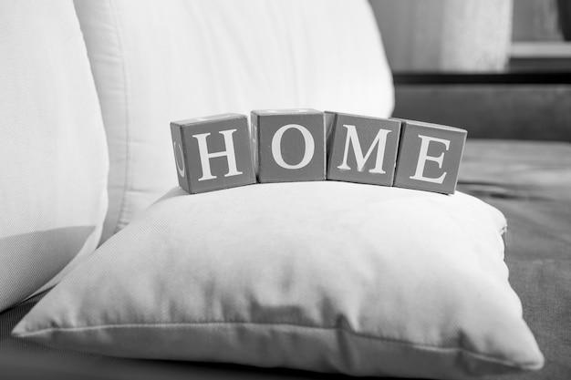 Крупным планом черно-белое фото слова дом написано на деревянных кубиках