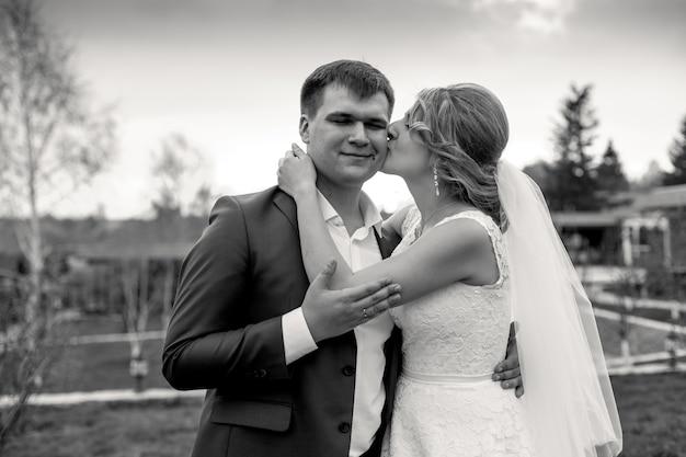 신랑의 뺨에 키스를주는 신부의 근접 촬영 흑백 초상화