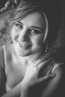 란제리에 귀여운 웃는 여자의 근접 촬영 흑백 초상화