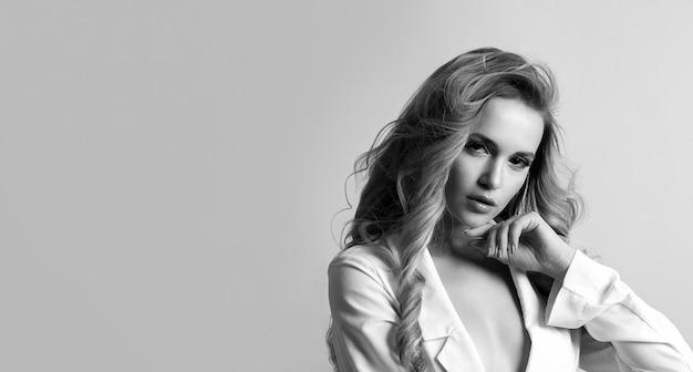 巻き毛と裸の肩を持つ素晴らしい若い女性のクローズアップの黒と白のショット。テキスト用のスペース