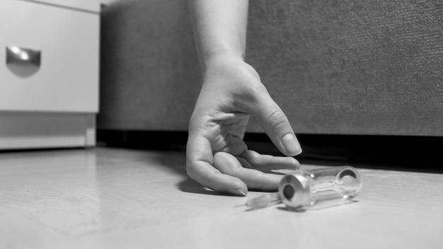 Крупным планом черно-белый вид руки наркозависимой женщины, лежащей на полу рядом с использованным шприцем.