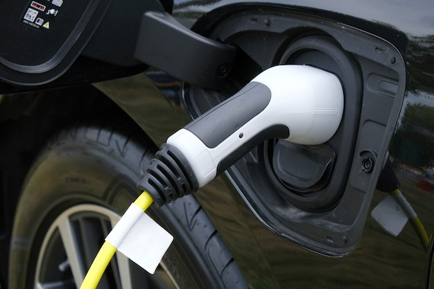 Closeup of black electric car charging in station.